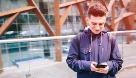 使用手机室外城市街道,年轻可爱的学生偶然蓝色衬衣谈话的英俊的人 免版税图库摄影