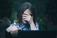 使用手机害怕的和绝望痛苦网上恶习cyberbullying的被偷偷靠近的年轻哀伤的脆弱的女孩 免版税库存照片