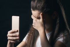 使用手机害怕的和绝望痛苦网上恶习cyberbullying的被偷偷靠近的年轻哀伤的脆弱的女孩 免版税库存图片
