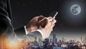 使用手机有全景都市风景的在日出和夜空的商人与满月和星 免版税库存照片