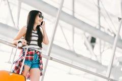 使用手机电话的年轻亚裔旅客妇女或大学生在有行李的机场 海外旅游研究或概念 免版税库存照片