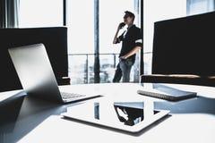 使用手机电话的男性亚洲小企业主在有膝上型计算机的现代办公室 项目管理,通信概念 免版税库存照片