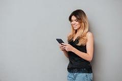 使用手机的一个年轻偶然女孩的画象 免版税库存照片