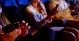 使用手机的不同种族的商人在企业研讨会期间在观众席4 4k 股票录像