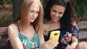 使用手机的两个不同种族的女孩,当坐长凳时 免版税图库摄影