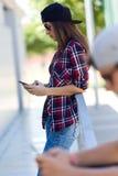 使用手机的两位溜冰者在街道 免版税库存图片