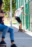 使用手机的两位溜冰者在街道 免版税库存照片