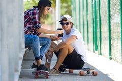 使用手机的两位溜冰者在街道 库存图片