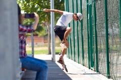 使用手机的两位溜冰者在街道 图库摄影