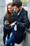 使用手机的两名学生在街道 库存图片