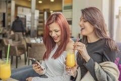 使用手机的两名年轻迷人的妇女和获得乐趣在co 免版税库存照片