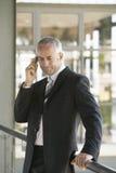使用手机的严肃的商人 免版税库存图片