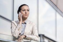 使用手机的严肃的年轻女实业家在办公室栏杆 库存图片