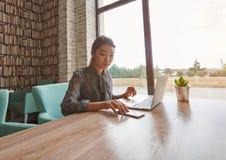 使用手机的中国妇女,当放松在便携式的网书时的工作以后 免版税库存图片