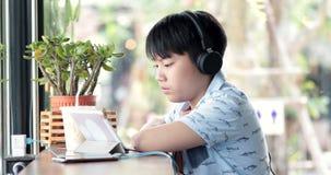 使用手机的亚裔逗人喜爱的男孩和啜饮牛奶在杯子和微笑 股票视频