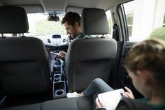 使用手机的人在汽车,当坐在后座时的十几岁的女孩 图库摄影