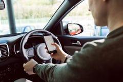 使用手机的人的中央部位在汽车 库存照片