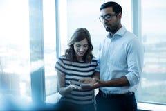 使用手机的企业夫妇反对玻璃窗 图库摄影