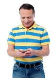 使用手机的偶然年迈的人 免版税图库摄影