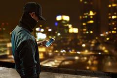 使用手机的匿名黑客 免版税库存图片