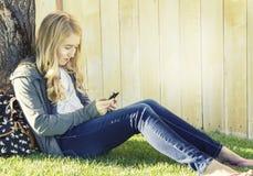 使用手机的十几岁的女孩 免版税库存照片
