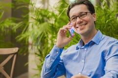 使用手机的可爱和英俊的商人,有亚洲的商人电话谈话 免版税库存照片