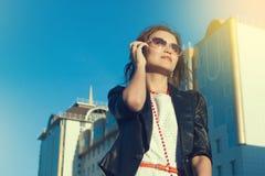 使用手机的可爱的女实业家在城市在sanny天 免版税图库摄影