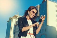 使用手机的可爱的女实业家在城市在sanny天 免版税库存照片