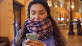 使用手机的可爱的年轻混合的族种微笑的妇女在夜圣彼得堡街道上的步行期间  4K 影视素材