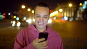 使用手机的可爱的西班牙人 英俊的人键入的智能手机都市街市夜点燃通信 影视素材
