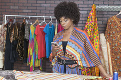 使用手机的可爱的非裔美国人的女性时装设计师 免版税库存照片