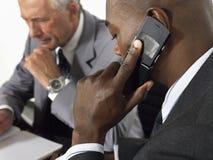 使用手机的商人在会议 免版税库存图片