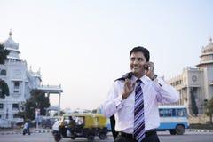 使用手机的商人在城市街道上 免版税库存图片