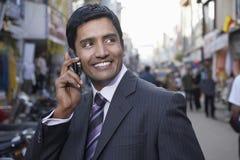 使用手机的商人在城市街道上 图库摄影