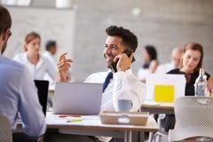 使用手机的商人在繁忙的办公室 免版税库存图片