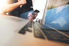 使用手机的商人手有作为busi的便携式计算机的 库存图片