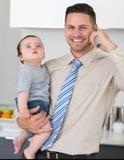 使用手机的商人,当运载婴孩在房子里时 免版税库存照片
