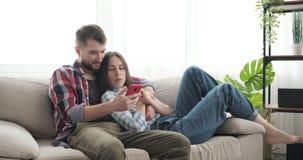 使用手机的夫妇在沙发在家 影视素材
