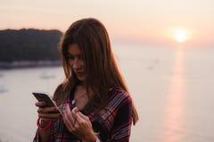 使用手机的女孩在海附近在日出或日落 免版税库存图片
