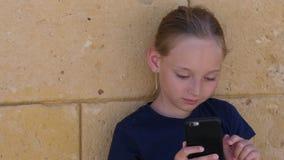 使用手机的女孩少年为与朋友的通信在社会网络 股票录像