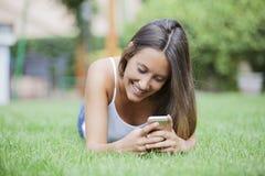 使用手机的女孩,当说谎在草时 免版税库存图片