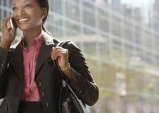 使用手机的女实业家反对大厦 免版税库存图片
