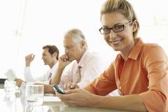 使用手机的女实业家在会议室 免版税库存图片