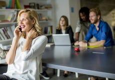 使用手机的女实业家在办公室和其它事项pe 免版税图库摄影