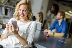 使用手机的女实业家在办公室 库存图片
