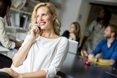 使用手机的女实业家在办公室 免版税库存图片