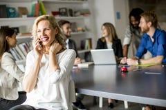 使用手机的女实业家在办公室 免版税图库摄影