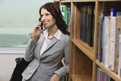 使用手机的女实业家在图书馆 免版税库存照片