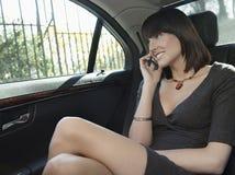 使用手机的女实业家在汽车 库存照片