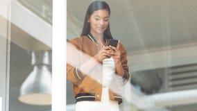 使用手机的女实业家在窗口附近在一个现代办公室 免版税库存照片